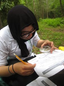 Marwa Hassan of Riverside High School in Durham studying stream ecology as part of a two-week summer science program in Pisgah National Forest. Photo by Savannah Midgette.