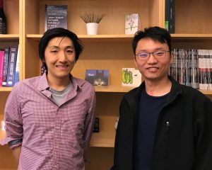 A photo of graduate students Junu Bae and Zijian Zhou in front of a bookshelf.